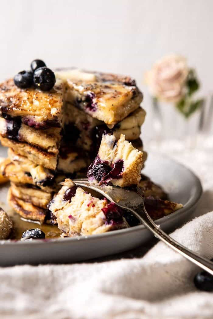 Blueberry Lemon Ricotta Pancakes with fork in pancakes and bite taken out