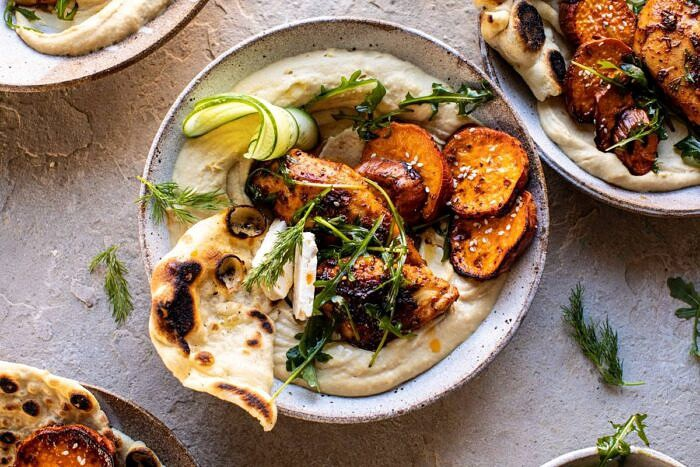 horizontal photo of Sheet Pan Chicken Shawarma with Sesame Sweet Potatoes and Hummus in bowls