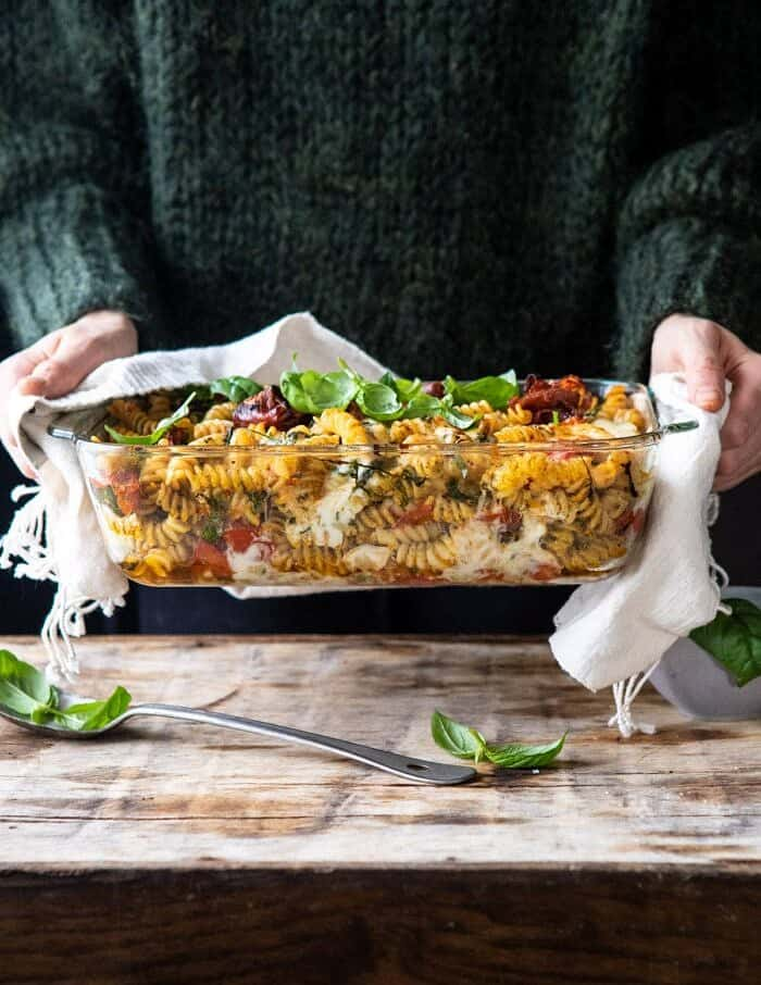 front on photo of Caprese Pesto Pasta Bake with person holding baking dish