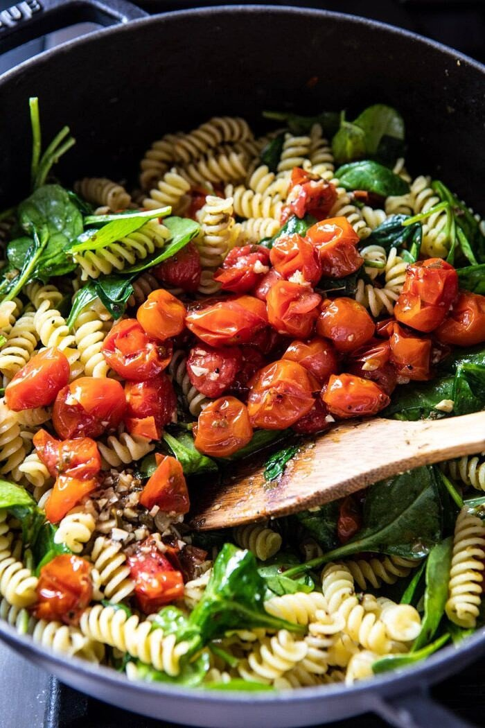 Caprese Pesto Pasta being tossed together in bowl