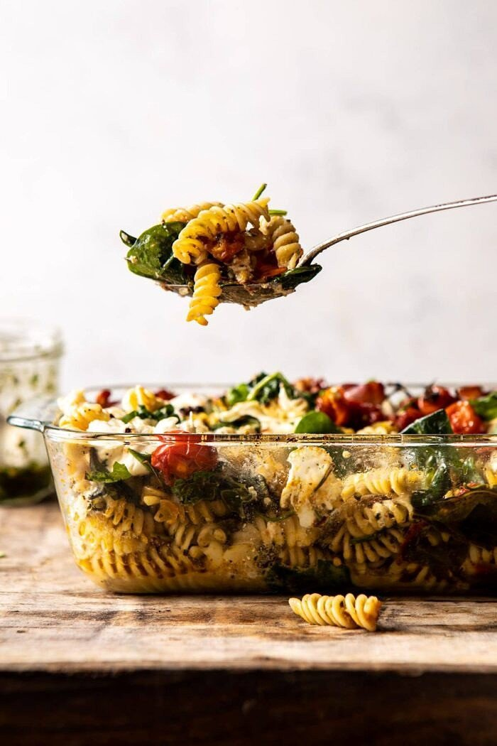 side angled photo of Caprese Pesto Pasta Bake with spoon coming out of dish