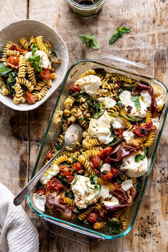 overhead photo of Caprese Pesto Pasta Bake with bowl of food on surface