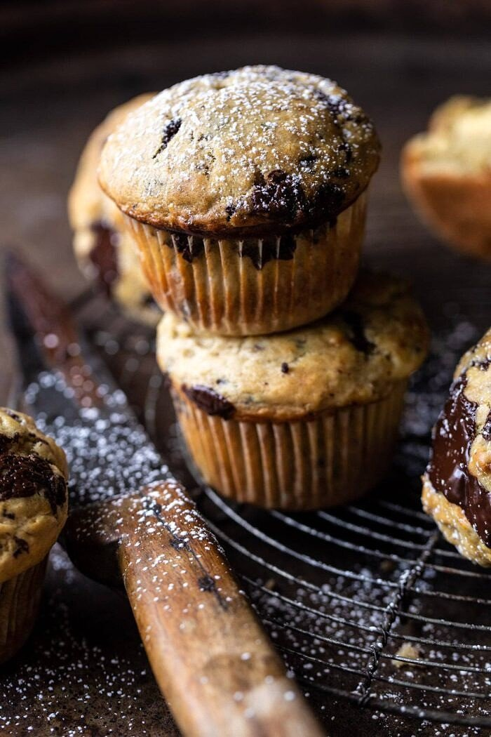 close up photo of Cheesecake Stuffed Chocolate Chunk Banana Bread Muffins 2 stacked on each other