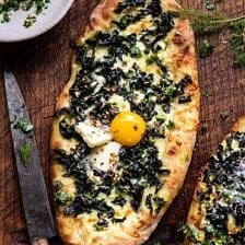 Khachapuri (Georgian Cheese Bread) with Kale and Herb Sauce.