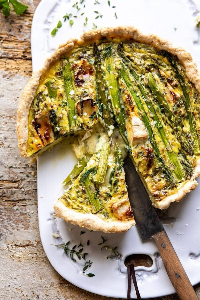 overhead photo of Asparagus and Brie Quiche with 1 slice cut and knife in quiche