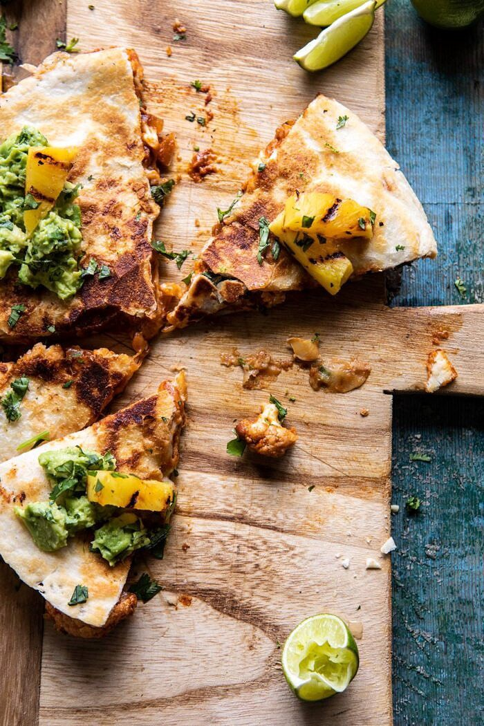 overhead photo of Cauliflower Al Pastor Quesadillas with Lime Smashed Avocado half eaten