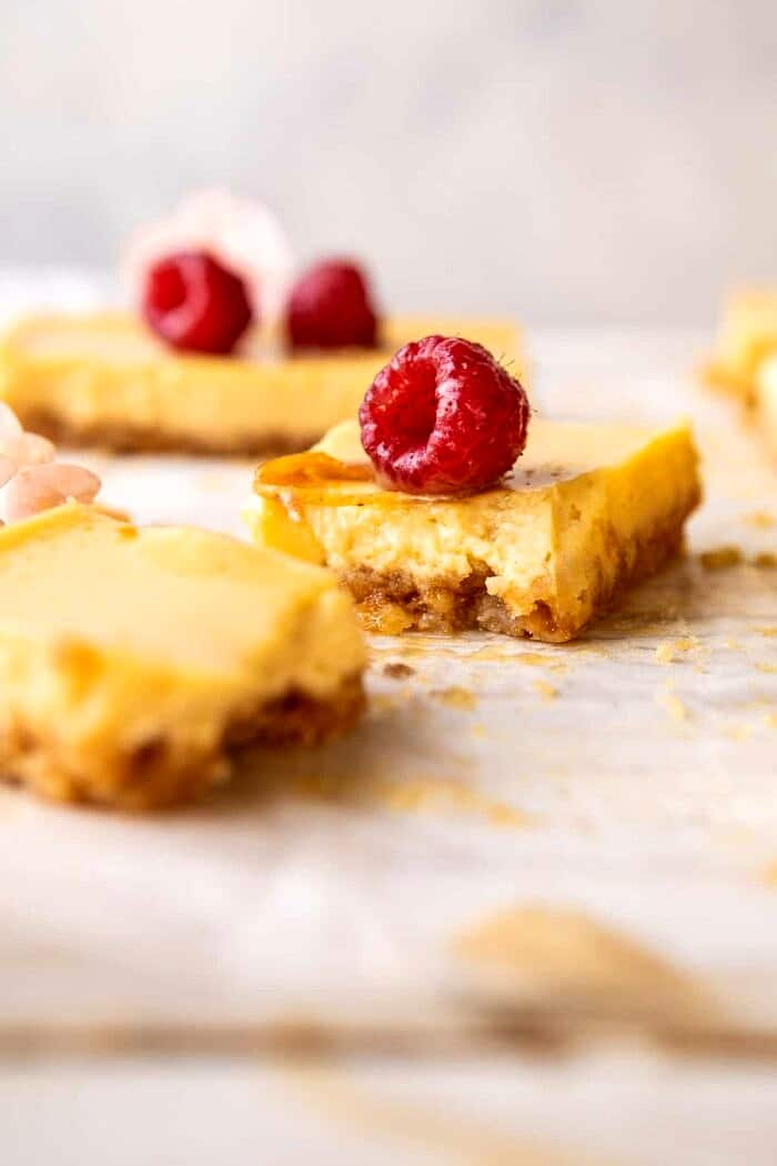 side angled photo of broken in half Creamy Lemon Bars with Browned Butter Raspberries