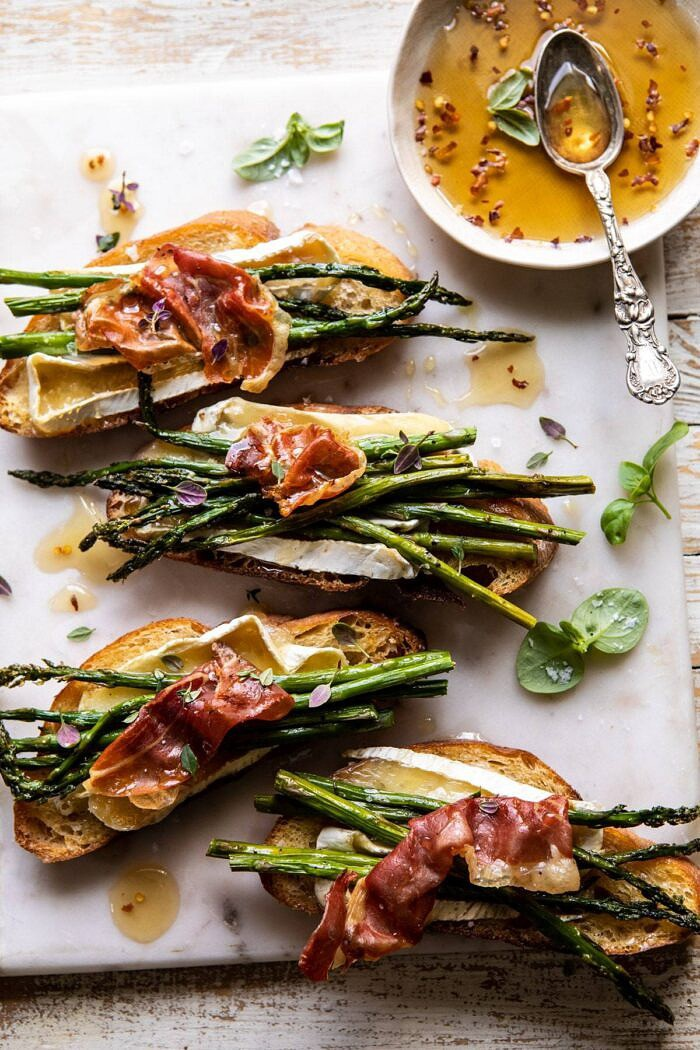 overhead photo of Crispy Prosciutto, Asparagus, and Brie Toast with hot honey in photo