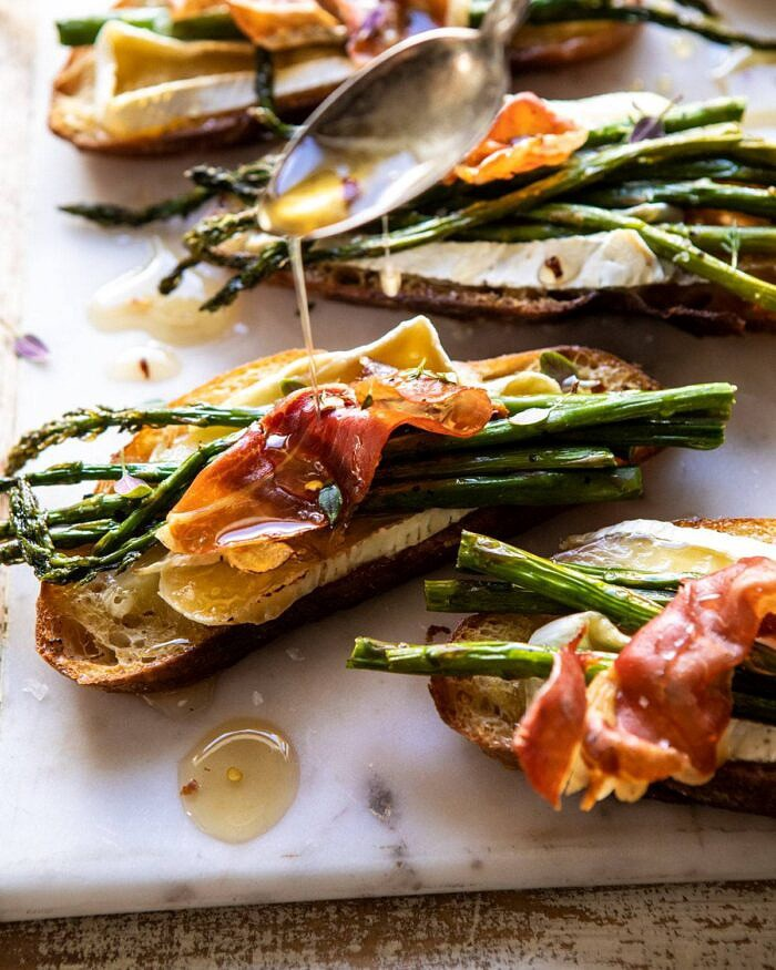 side angled photo of Crispy Prosciutto, Asparagus, and Brie Toast with honey being drizzled over the toast