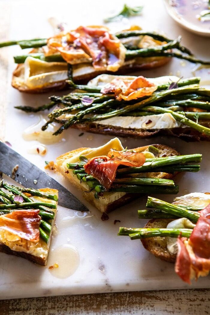 side angled photo of Crispy Prosciutto, Asparagus, and Brie Toast cut in half