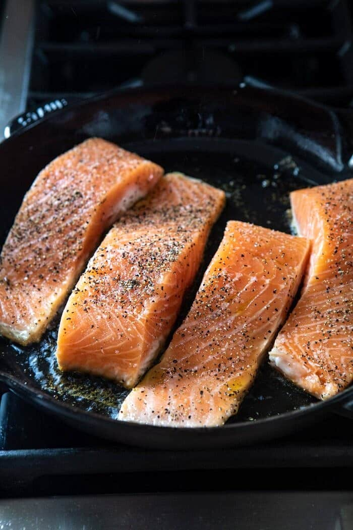 raw salmon cooking in skillet