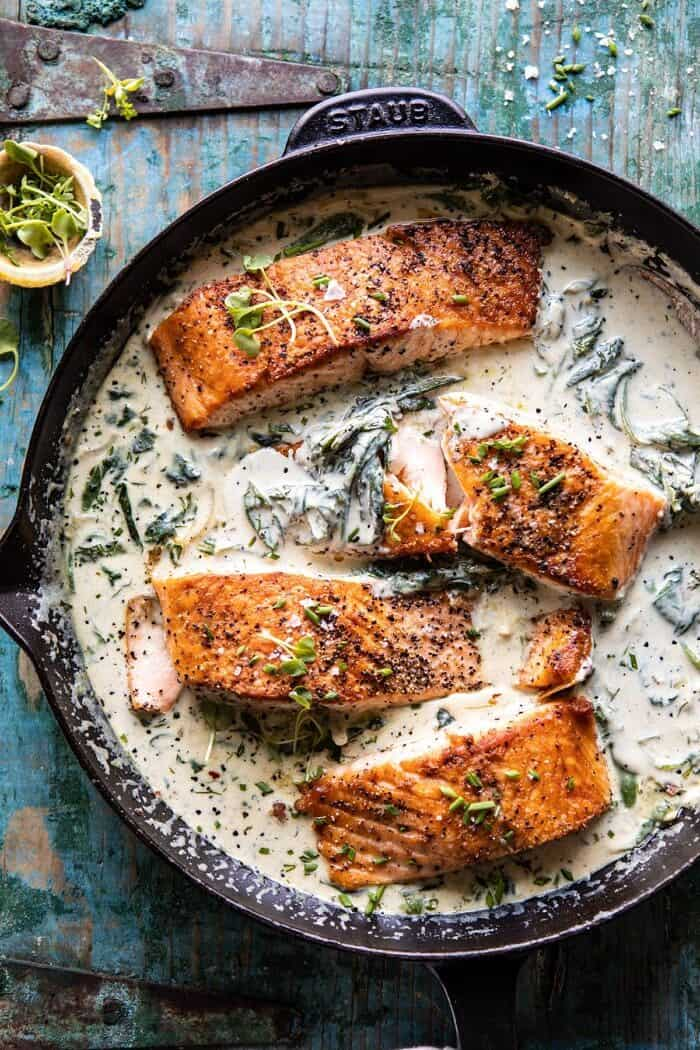 Garlic Butter Creamed Spinach Salmon in skillet with 1 salmon filet broken in half