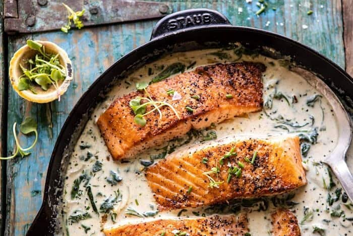 horizontal photo of Garlic Butter Creamed Spinach Salmon in skillet