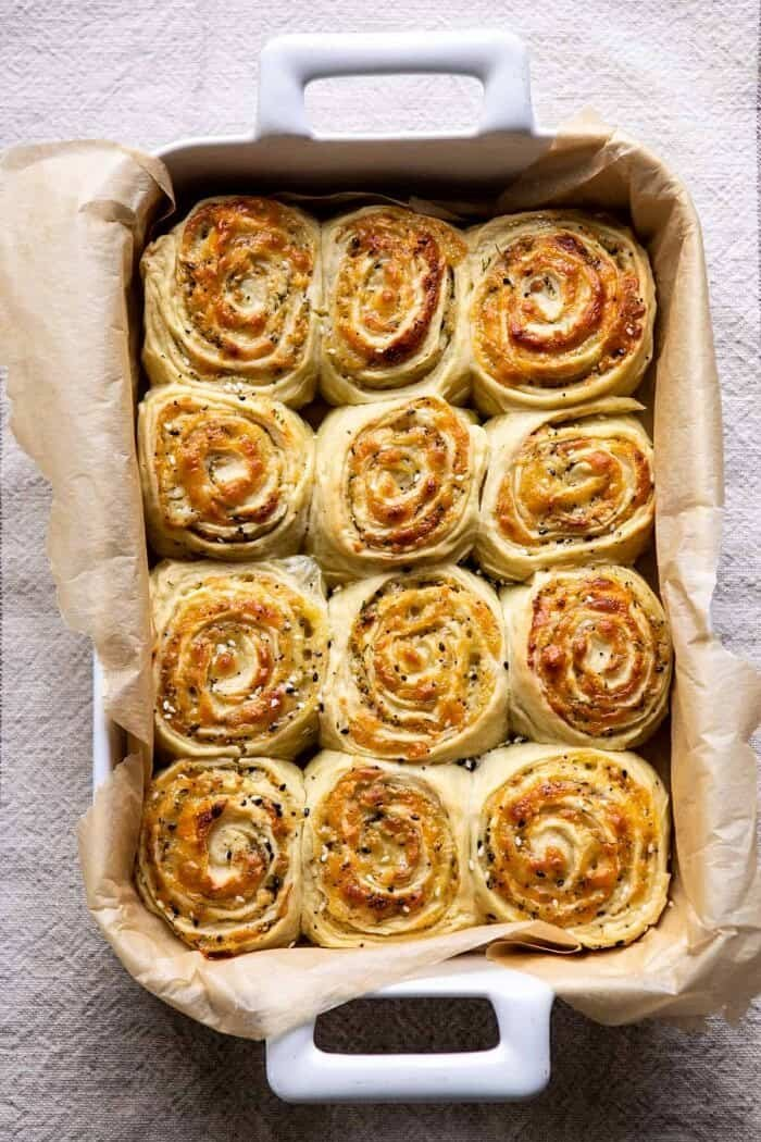 Herby Everything Cheddar Swirl Buns in baking dish