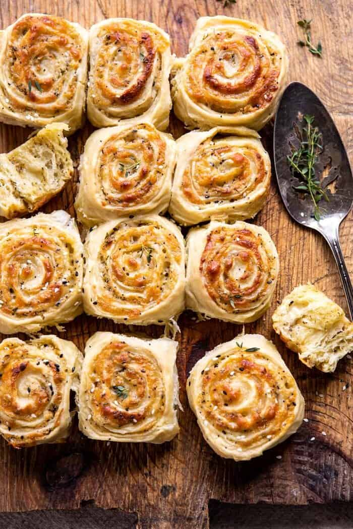 overhead Herby Everything Cheddar Swirl Buns with serving spoon and herbs