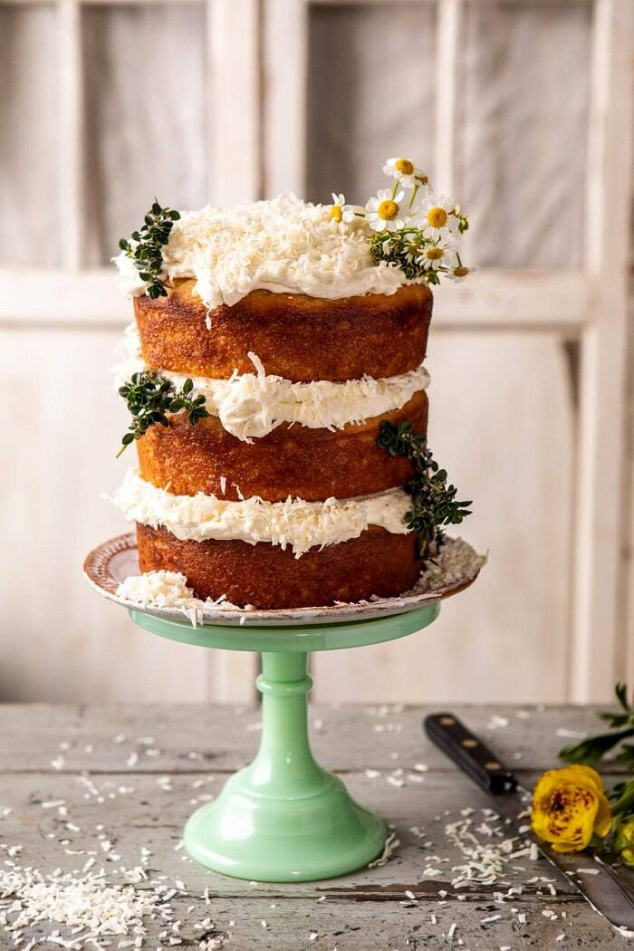 side angled photo of Lemon Coconut Naked Cake with Whipped Vanilla Buttercream on cake stand