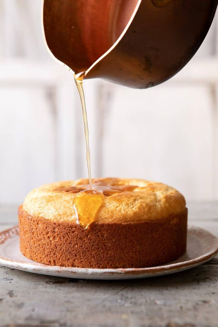 lemon honey syrup being drizzled on Lemon Coconut Naked Cake
