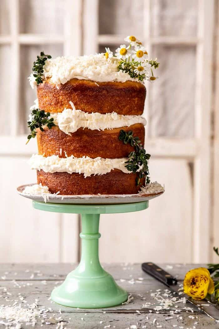 side angled photo of Lemon Coconut Naked Cake with Whipped Vanilla Buttercream on cake stand and flowers on table