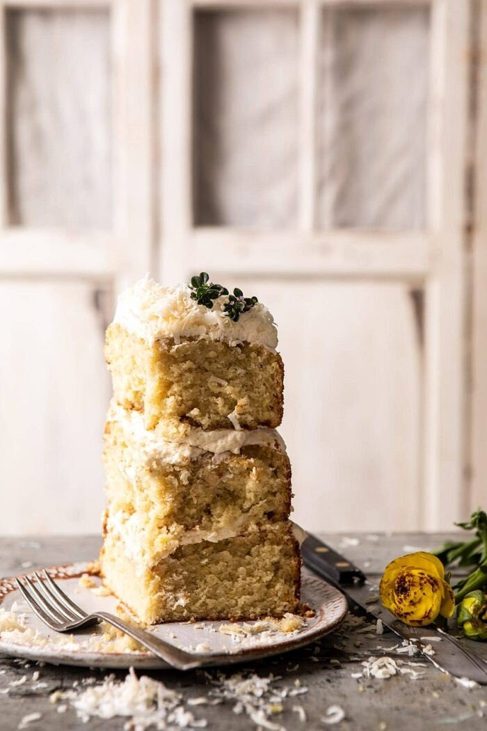 Lemon Coconut Naked Cake piece standing up on dessert plate with fork on plate