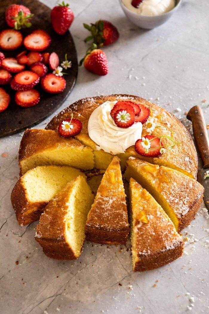 side angled photo of Strawberry Chamomile Olive Oil Cake with Honeyed Ricotta with 6 slices cut out