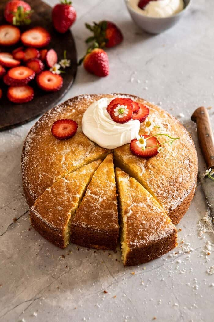 side angled photo of Strawberry Chamomile Olive Oil Cake with Honeyed Ricotta and 3 slices cut