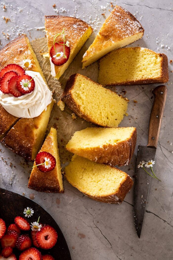 over head photo ofo Strawberry Chamomile Olive Oil Cake with Honeyed Ricotta and 8 slices cut from cake and knife in photo