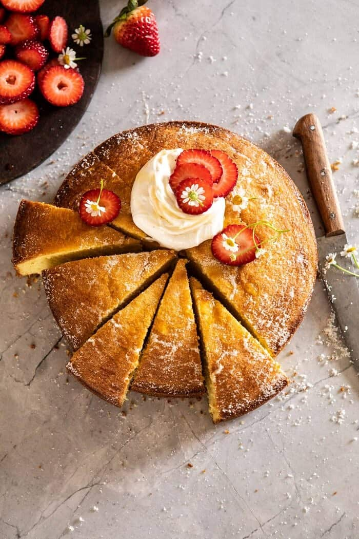 overhead photo of Strawberry Chamomile Olive Oil Cake with Honeyed Ricotta and 6 slices cut from cake