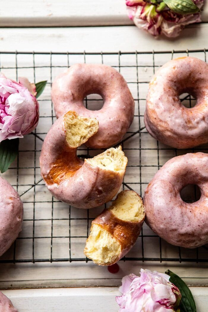 Strawberry Glazed Chai Doughnuts with bite taken out of doughnut