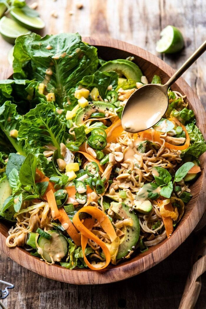 Thai Peanut Chicken Ramen Noodle Salad with spoon drizzling on peanut sauce