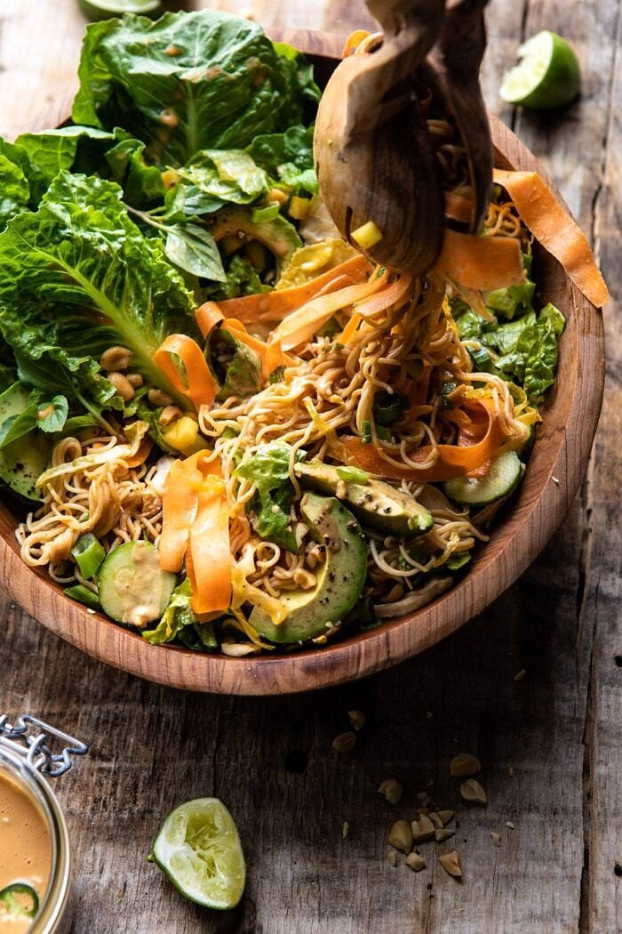 Thai Peanut Chicken Ramen Noodle Salad with tongs pulling up noodles out of bowl