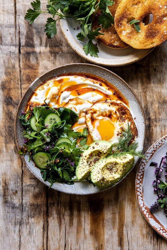 overhead photo if Turkish Eggs with Chile Butter and Whipped Feta with bagel and greens in photo