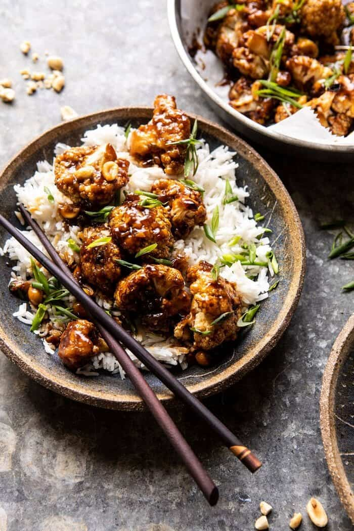 side angled close up photo of Better Than Takeout Kung Pao Cauliflower in a bowl with rice an chopsticks