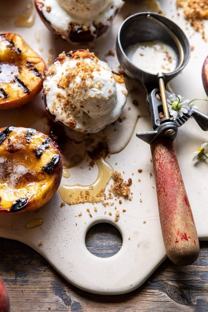 close up side angled photo of Browned Butter Grilled Peaches with Cinnamon Toast Brioche Crumbs on serving plate with ice cream scoop