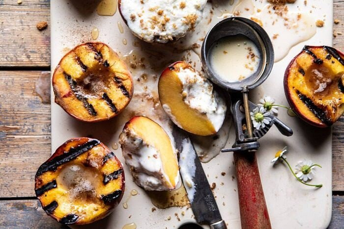 horizontal photo of Browned Butter Grilled Peach cut in half with Cinnamon Toast Brioche Crumbs