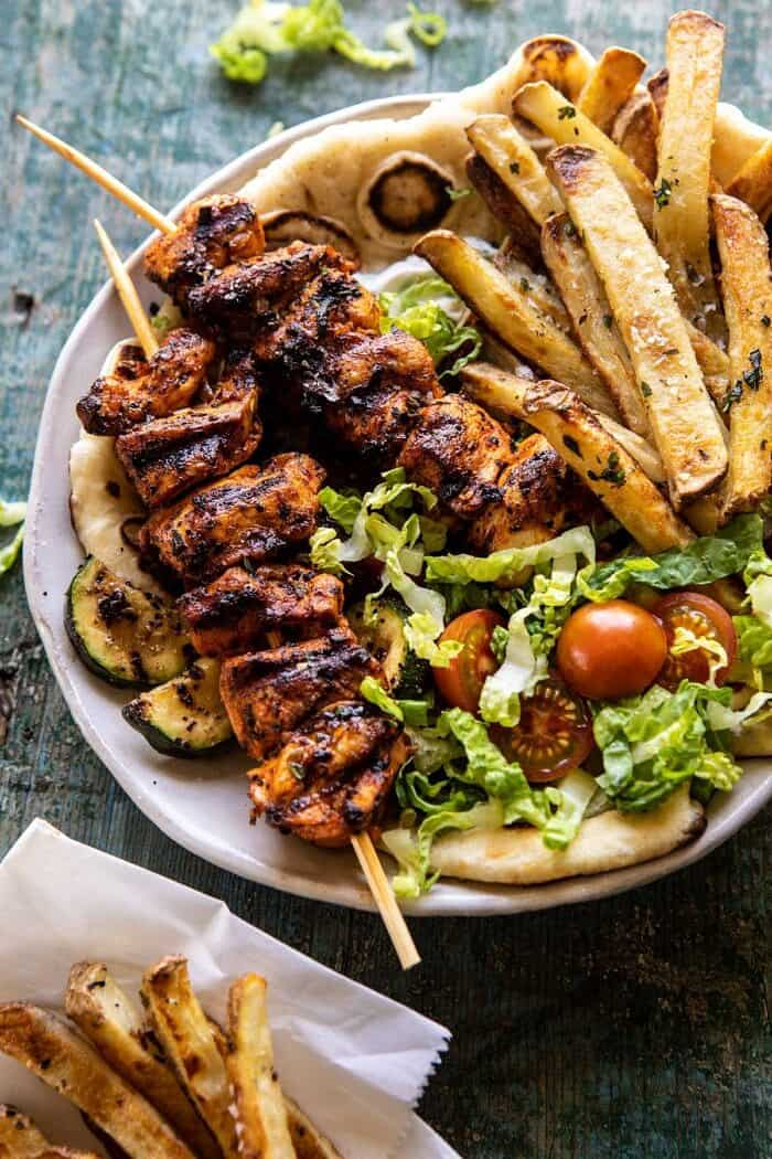 overhead close up photo of Chicken Souvlaki Bowls with Garlic Fries