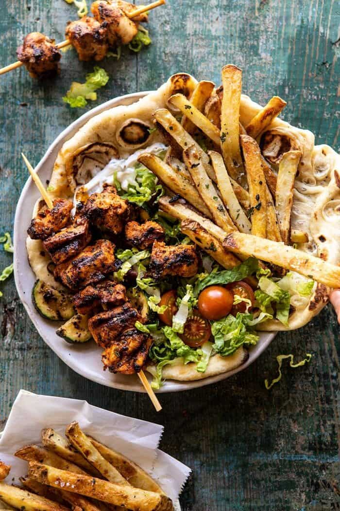 overhead photo of Chicken Souvlaki Bowls with Garlic Fries and chicken off of stick in bowl