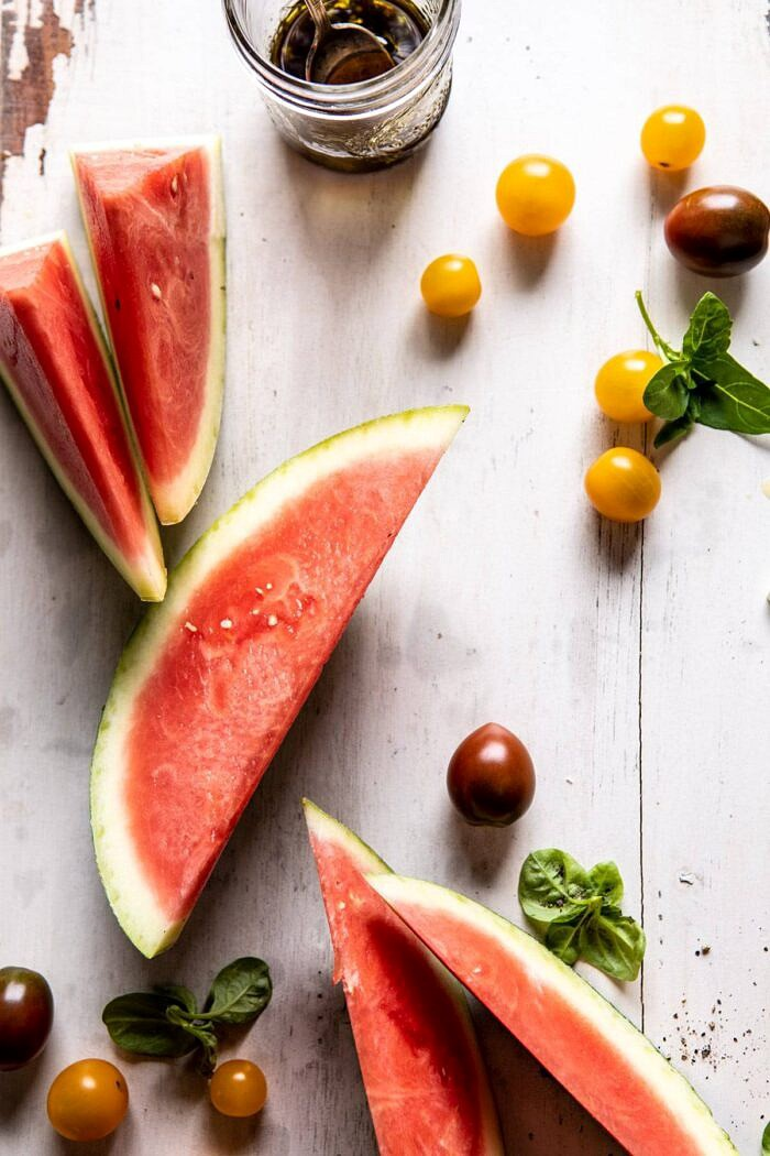 Watermelon and tomatoes on cutting board