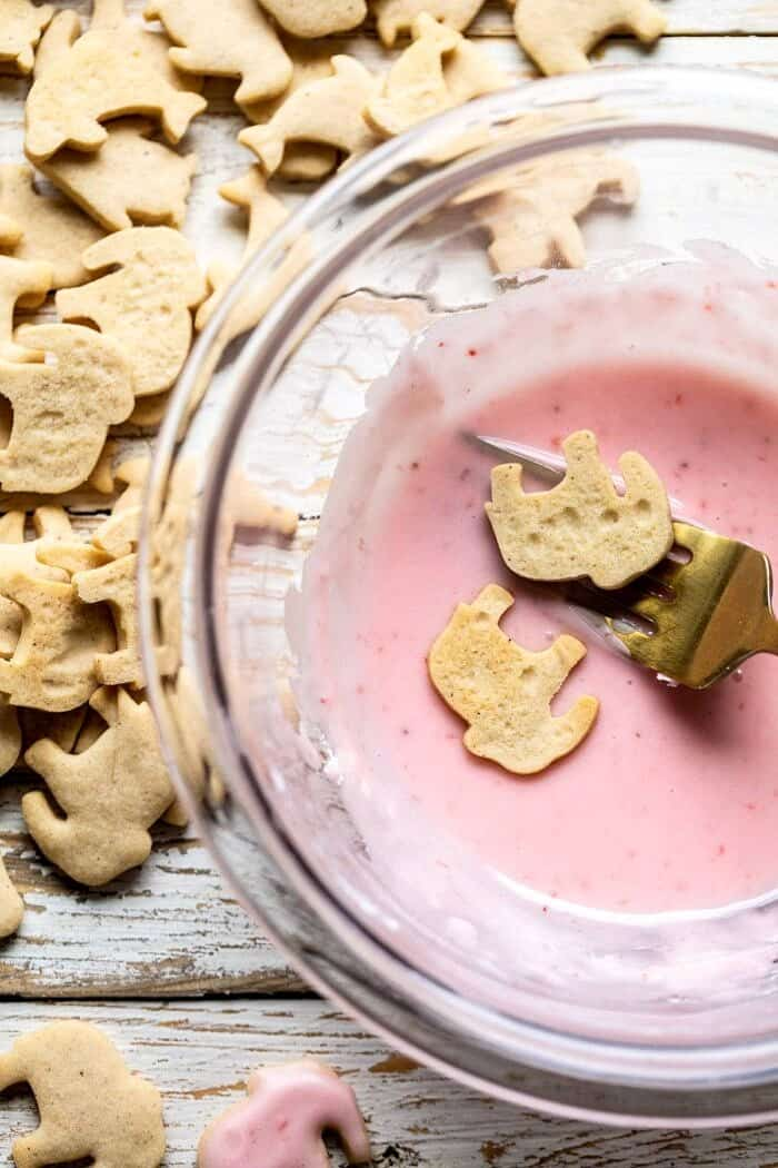 Homemade Animal Crackers being dipped in pink strawberry glaze