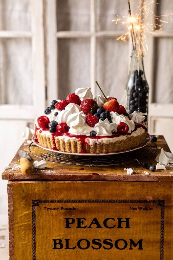 head on photo of No-Bake Eton Mess Berry Cheesecake with sparklers in background of photo