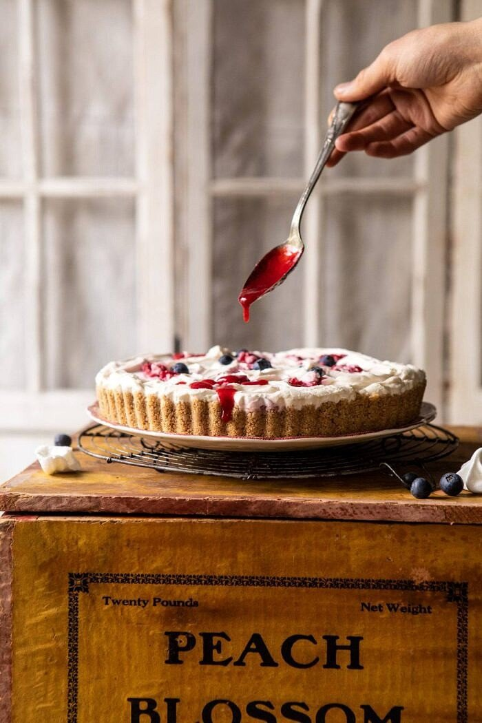head on photo of No-Bake Eton Mess Berry Cheesecake with raspberry sauce being drizzled over cake