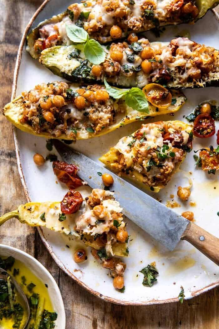 overhead photo of Spicy Chickpea and Cheese Stuffed Zucchini with zucchini cut in half and filling spilling out