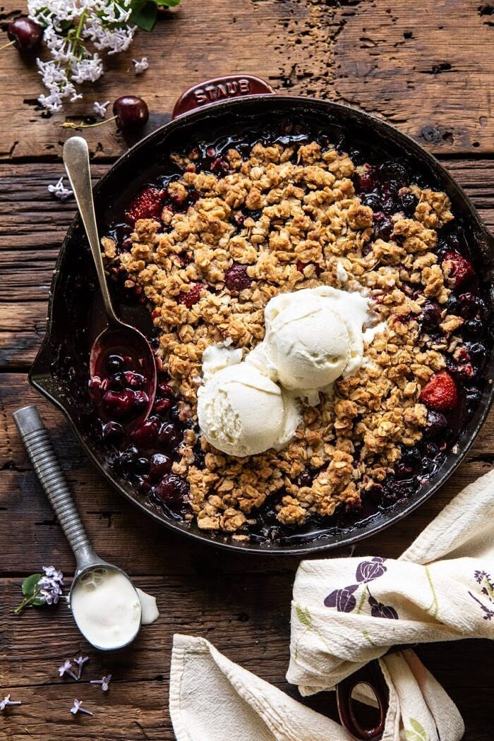 overhead photo of Buttery Cherry Berry Skillet Crisp with ice cream on crisp and spoon in skillet