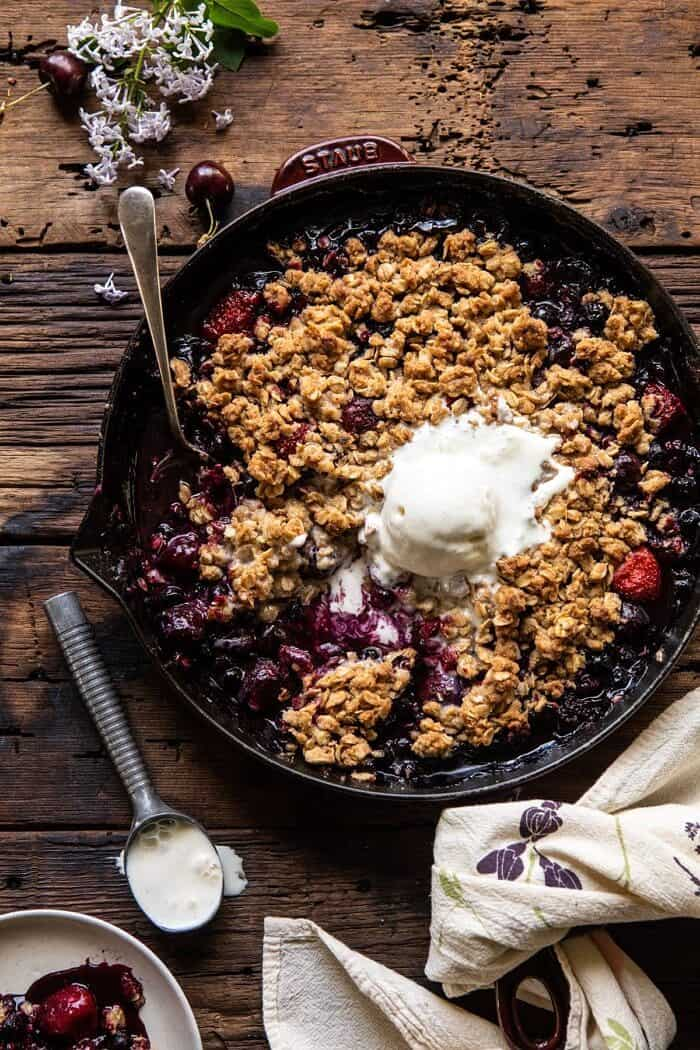 overhead photo of Buttery Cherry Berry Skillet Crisp in skillet with 1 scoop of ice cream and spoon in skillet