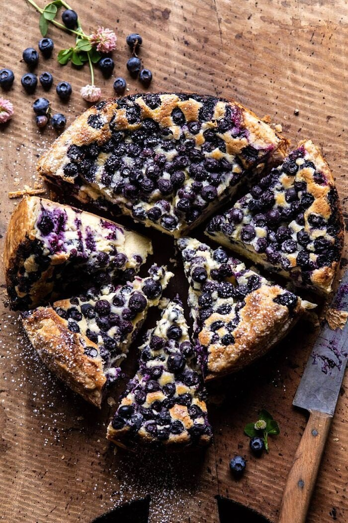 overhead photo of Simple Blueberry Basque Cheesecake with 4 slices of cake cute and berries on surface
