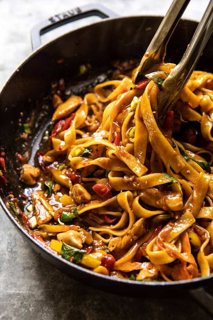 side angle photo of Better Than Takeout Thai Drunken Noodles in cooking pot with tongs pulling the noodles out of the pot