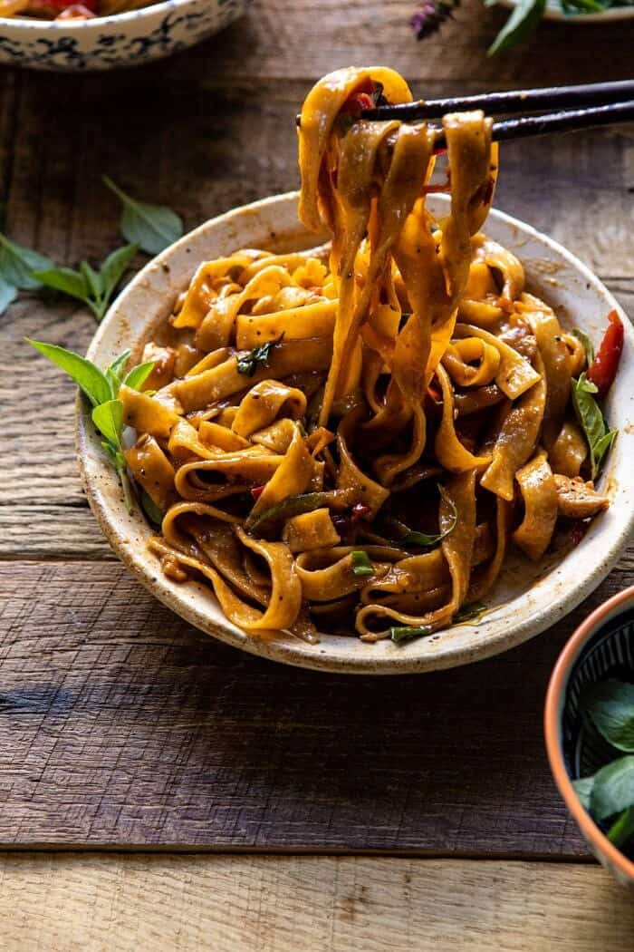 side angled photo of Better Than Takeout Thai Drunken Noodles with chopsticks pulling noodles out of the bowl to eat