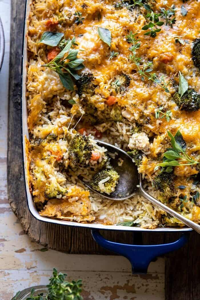 overhead close up photo of Broccoli Cheddar Chicken and Rice Casserole with serving spoon in casserole dish