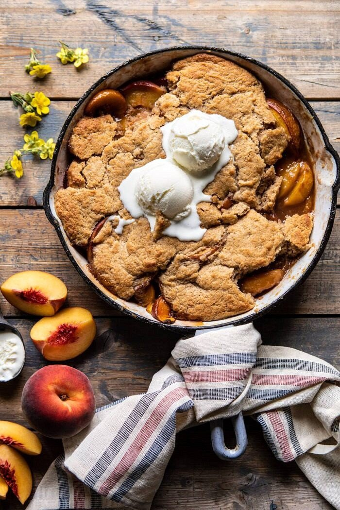 overhead photo of Skillet Brown Sugar Peach Cobbler with 2 scoops of ice cream on top