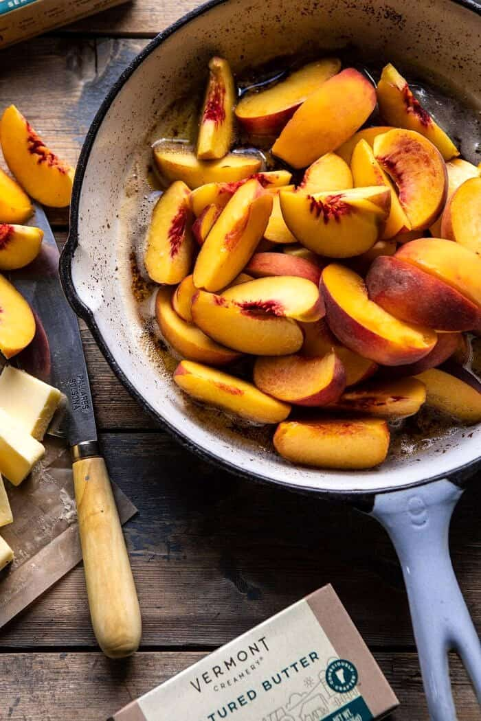 overhead photo of sliced peaches in skillet with browned butter before baking