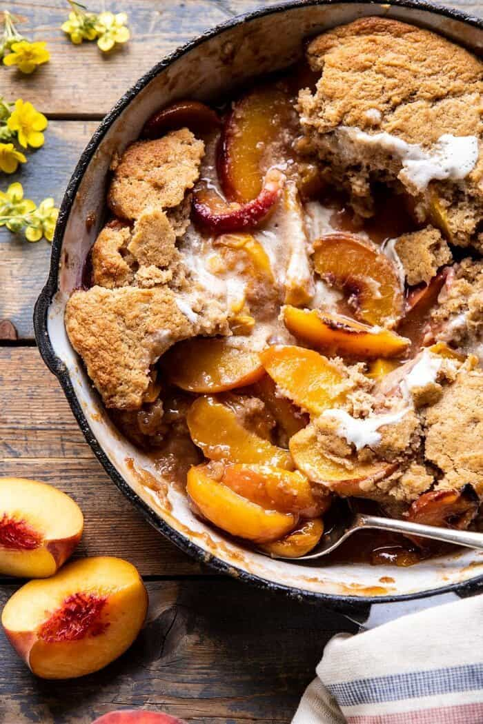overhead close up photo of Skillet Brown Sugar Peach Cobbler with spoonfuls removed from cobbler